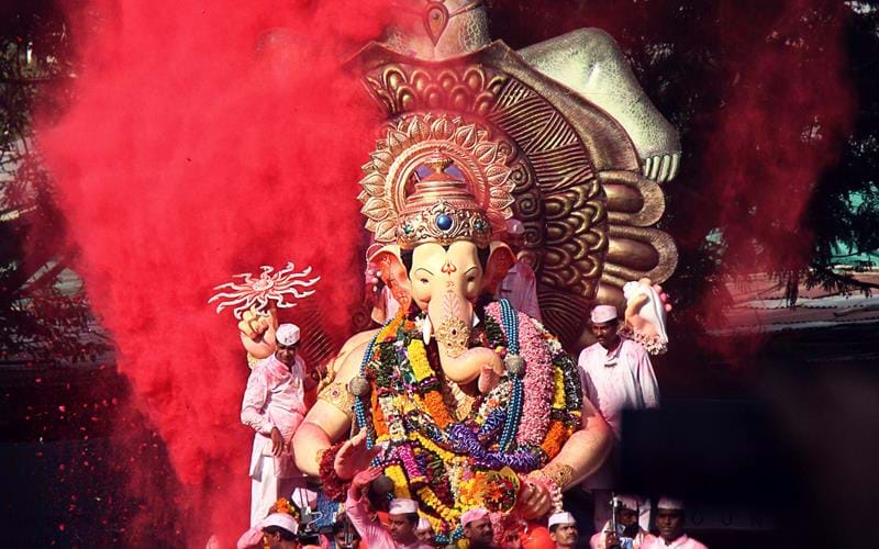 A statue of Ganesh is paraded through the streets during a colourful monsoon festival