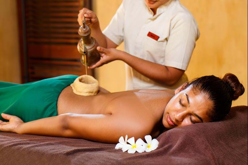 A woman enjoying an Ayurvedic treatment with oil